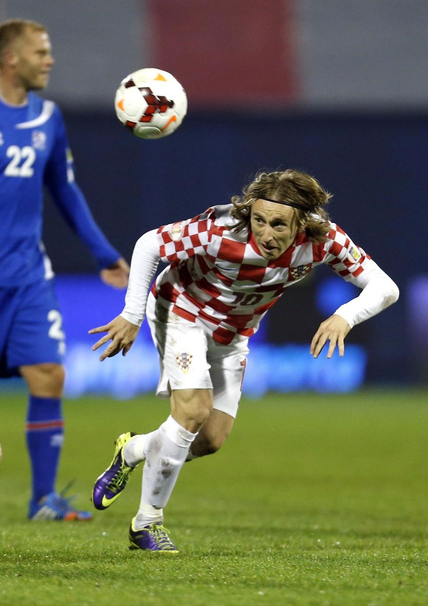 FILE - In this Nov. 19, 2013, file photo, Croatia's Luka Modric heads the ball during their World Cup qualifying playoff second leg soccer match with Iceland, in Zagreb, Croatia. (AP Photo/Darko Bandic, File)