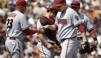 Arizona Diamondbacks pitcher Trevor Cahill, right, walks off the mound after being relieved by manager Kirk Gibson (23) during the fourth inning of a baseball game against the San Francisco Giants in San Francisco, Tuesday, April 8, 2014. The Giants won 7-3. Cahill was the losing pitcher. (AP Photo/Eric Risberg)