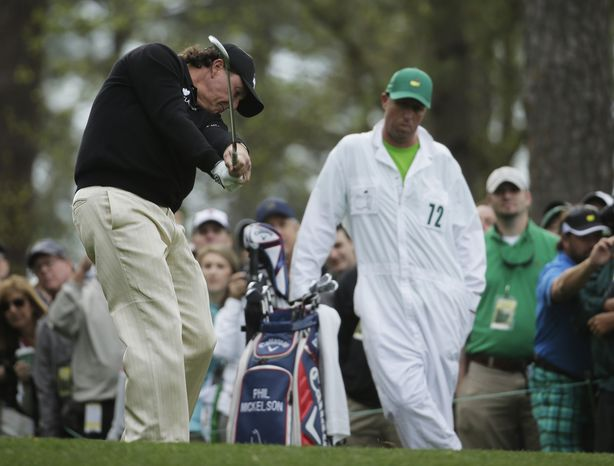 Caddy Jim MacKay, right, watches as Phil Mickelson tee off on the fourth hole during a practice round for the Masters golf tournament Tuesday, April 8, 2014, in Augusta, Ga. (AP Photo/Chris Carlson)