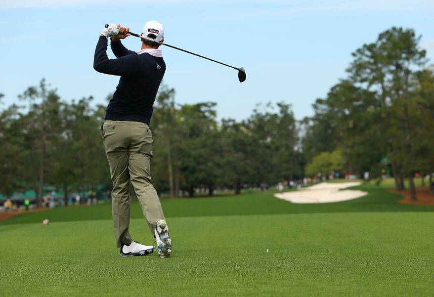 The 2013 Masters champion Adam Scott, of Australia, hits on the first hole to begin practice for the Masters golf tournament at Augusta National on Tuesday, April 8, 2014, in Augusta, Ga. (AP Photo/Atlanta Journal-Constitution, Curtis Compton)