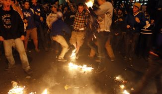 Kentucky fans gather at the intersection of Elizabeth and State Streets near campus in Lexington, Ky.,  and burn shirts after losing the NCAA College basketball Championship game to UConn Monday, April 7, 2014.  (AP Photo/The Courier-Journal,  James Crisp)