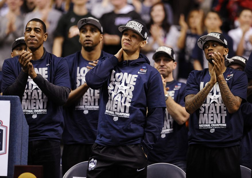 Connecticut's Shabazz Napier, center, reacts as his name is revealed on the Huskies Wall of Honor as head coach Kevin Ollie, left, and Ryan Boatright, right, applaud at a pep rally celebrating the program's fourth national championship, Tuesday, April 8, 2014, in Storrs, Conn. (AP Photo/Jessica Hill)