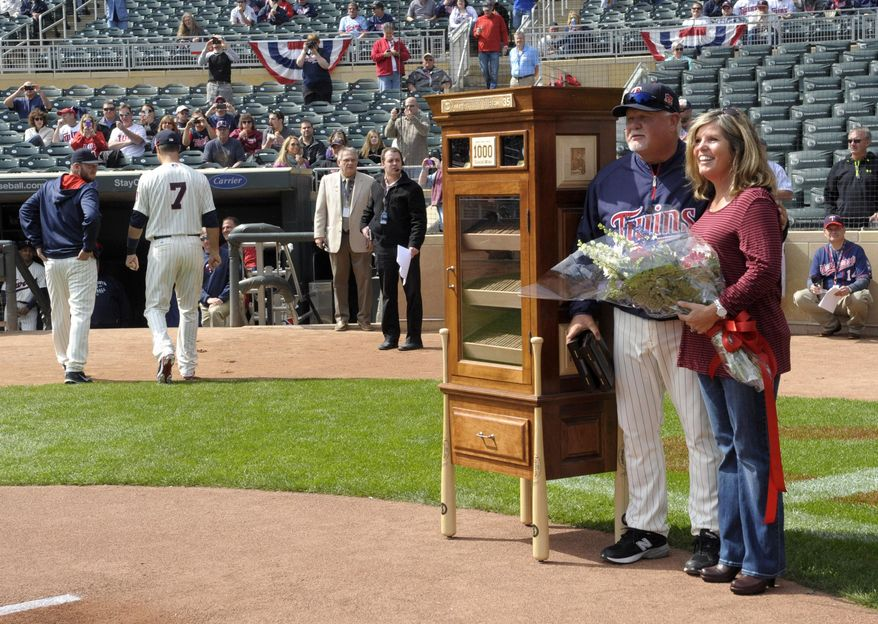 Minnesota Twins manager Ron Gardenhire and his wife, Carol, pose with a humidor filled with cigars in recognition of his 1000th win prior to the Twins baseball game against the Oakland Athletics, Wednesday, April 9, 2014 in Minneapolis. (AP Photo/Tom Olmscheid)