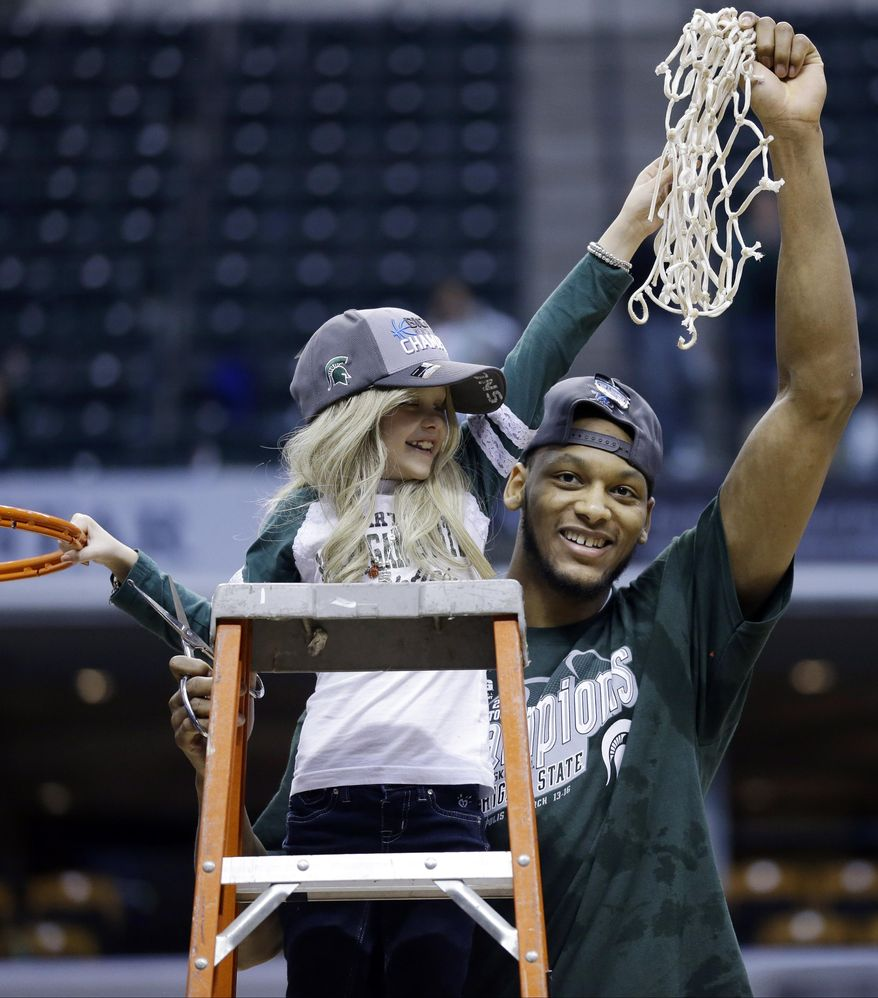 ** FILE ** In this March 16, 2014, file photo, Michigan State forward Adreian Payne, right, hoists the net with Lacey Holsworth, who is battling cancer, after Michigan State defeated Michigan 69-55 in an NCAA college basketball game in the championship of the Big Ten Conference tournament in Indianapolis. The father of  8-year-old Lacey Holsworth, who befriended Michigan State basketball star Adreian Payne, says his daughter has died. (AP Photo/Michael Conroy, File)