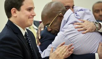 Jonathan Fleming, hugs his attorney Anthony Mayol while his other attorney Taylor Koss applaud in Brooklyn's Supreme court, after a judge declared him a free man on Tuesday April 8, 2014 in New York.  Fleming, who spent almost a quarter-century behind bars for murder, was cleared of a killing that happened when he was 1,100 miles away on a Disney World vacation in 1989. (AP Photo/Bebeto Matthews)