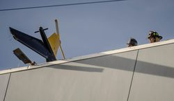 Firefighters study the helicopter  tail hanging over the edge of the UNM Hospital  Wednesday afternoon April 9, 2014, after it crashed as it took off from the roof of the building.     (AP Photo/The Albuquerque Journal, Roberto E. Rosales)  THE SANTA FE NEW MEXICAN OUT