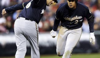 Milwaukee Brewers' Carlos Gomez (27) is greeted by third base coach Ed Sedar and scores on a solo home run in the fourth inning of a baseball game against the Philadelphia Phillies, Wednesday, April 9, 2014, in Philadelphia. (AP Photo/Michael Perez)