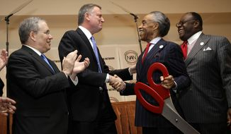 New York City Mayor Bill de Blasio, second from left, shakes hands with Rev. Al Sharpton, second from right, after using giant scissors for the ribbon cutting ceremony of the National Action Network convention in New York, Wednesday, April 9, 2014. Also participating in the ceremony are New York City Comptroller Scott Stringer, left, and Rev. Franklyn Richardson. (AP Photo/Seth Wenig)