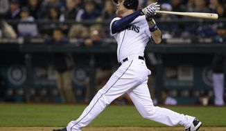 Seattle Mariners' Corey Hart watches a three-run home run in the third inning of a baseball game against the Los Angeles Angels on Tuesday, April 8, 2014, in Seattle. (AP Photo/Ted S. Warren)