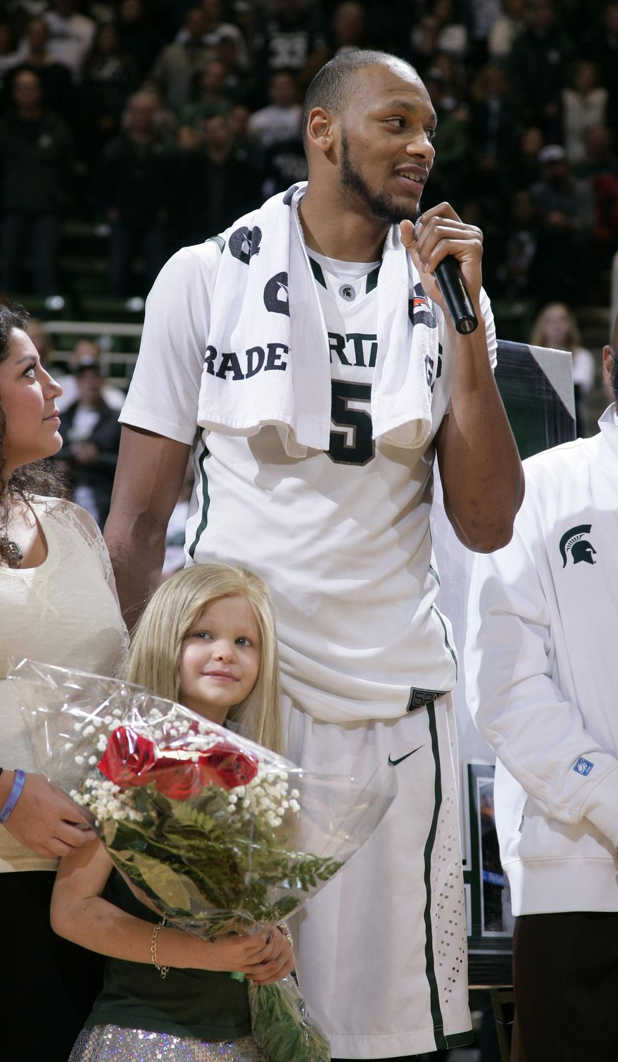 ** FILE ** In this March 6, 2014, file photo, Michigan State senior Adreian Payne addresses the crowd during a senior day ceremony as he stands with his guest, Lacey Holsworth, who is battling cancer, following an NCAA college basketball game against Iowa, in East Lansing, Mich. The father of  8-year-old Lacey Holsworth, who befriended Michigan State basketball star Adreian Payne says his daughter has died. (AP Photo/Al Goldis)