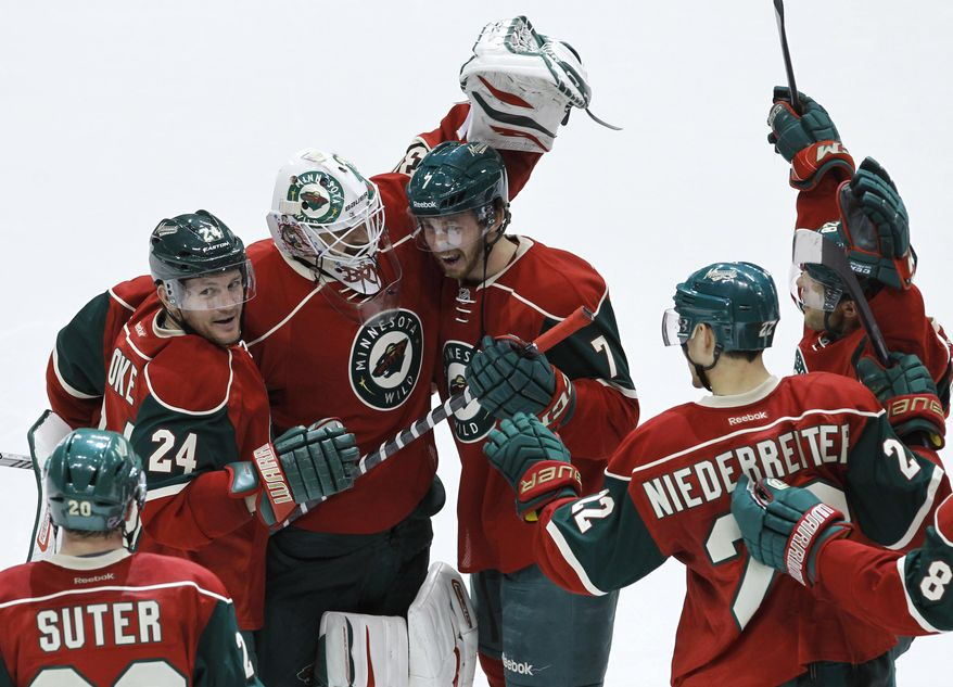 Minnesota Wild goalie Ilya Bryzgalov, of Russia, celebrates with teammates Matt Cooke (24), Jonathon Blum (7), Nino Niederreiter (22), of Switzerland, and others after the Wild defeated the Boston Bruins 4-3 during a shootout in an NHL hockey game in St. Paul, Minn., Tuesday, April 8, 2014.  (AP Photo/Ann Heisenfelt)