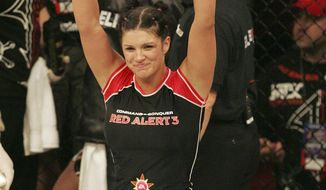 FILE - In this May 31, 2008, file photo, Gina Carano smiles after defeating Kaitlin Young in their EliteXC 140-pound bout in Newark, N.J. Carano was scheduled to meet with UFC President Dana White on Wednesday night, April 9, to discuss a return to mixed martial arts for a potential bout with bantamweight champion Ronda Rousey. (AP Photo/Rich Schultz, File)