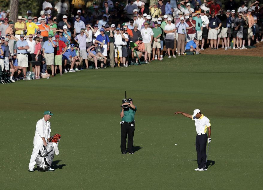 FILE - In this April 12, 2013 file photo, Tiger Woods takes a drop on the 15th hole after his ball went into the water during the second round of the Masters golf tournament in Augusta, Ga. Players as well as the rule officials come from all around the world to the Masters, making the official rulings as discussed as the score. (AP Photo/Charlie Riedel, File)