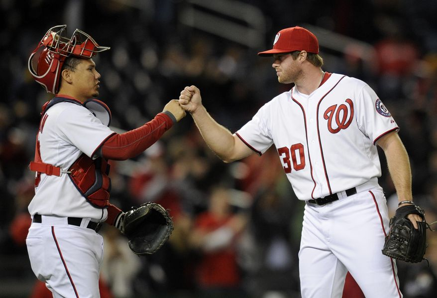 Washington Nationals relief pitcher Aaron Barrett (30) celebrates 5-0 win over the Miami Marlins with catcher Jose Lobaton, left, during the inning of a baseball game, Tuesday, April 8, 2014, in Washington. (AP Photo/Nick Wass)