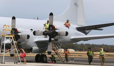 In this photo taken March 25, 2014, ground crew work on a Royal Australian Air Force P-3 Orion at RAAF Base Pearce after the aircraft returns from the search for the missing Malaysia Airlines Flight 370 in Perth, Australia. The ground crew typically work on the tarmac through the night so the planes are ready to fly again by daylight, as the international effort to find some trace of the missing jetliner continues. (AP Photo/Rob Griffith)
