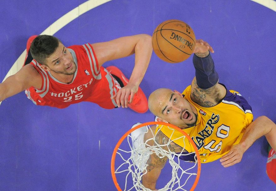 Los Angeles Lakers center Robert Sacre, right, shoots as Houston Rockets forward Chandler Parsons defends during the first half of an NBA basketball game, Tuesday, April 8, 2014, in Los Angeles. (AP Photo/Mark J. Terrill)