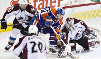 Colorado Avalanche goalie Jean-Sebastien Giguere (35) makes the save on Edmonton Oilers' Ryan Smyth (94) as Andre Benoit (61) and Nathan MacKinnon (29) chase the rebound during second period NHL hockey action in Edmonton, Alberta, on Tuesday April 8, 2014. (AP Photo/The Canadian Press, Jason Franson)