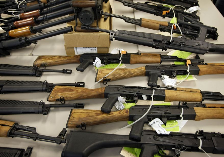 A cache of seized weapons is displayed Tuesday, Jan 25, 2011 in Phoenix. A grand jury has indicted 20 people on firearms charges for allegedly participating in a ring that bought more than 700 guns that were to be smuggled into Mexico for use by a drug cartel. (AP Photo/Matt York)