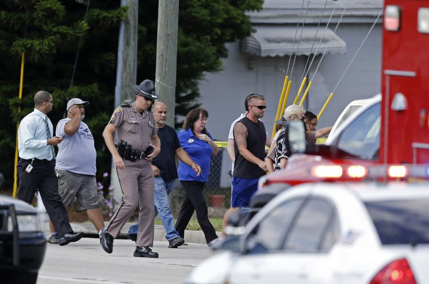A Florida state trooper, center, escorts a group of parents to a day care center to pick up their children after a vehicle crashed into the center, Wednesday, April 9, 2014, in Winter Park, Fla. At least 15 people were injured, including children. (AP Photo/John Raoux)