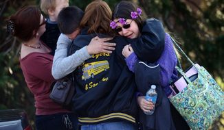 Parents and students embrace along School Road near Franklin Regional High School after more than a dozen students were stabbed by a knife wielding suspect at the school on Wednesday, April 9, 2014, in Murrysville, Pa., near Pittsburgh. The suspect, a male student, was taken into custody and is being questioned. (AP Photo/Tribune Review, Sean Stipp)