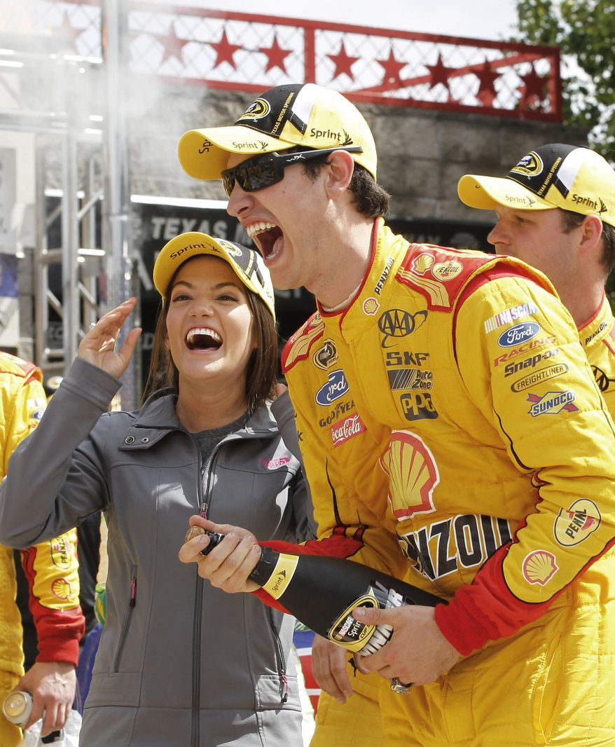 Joey Logano, right, celebrates in victory lane with his fiancee Brittany Baca after winning the NASCAR Sprint Cup Series auto race at Texas Motor Speedway Monday, April 7, 2014, in Fort Worth, Texas. (AP Photo/Mike Stone)