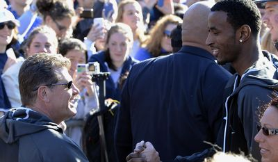 Connecticut women's basketball coach Geno Auriemma, left, is greeted by Connecticut men's basketball player DeAndre Daniels, right, after Auriemma arrived on campus with his team for a rally celebrating its NCAA championship, Wednesday, April 9, 2014, in Storrs, Conn. (AP Photo/Jessica Hill)