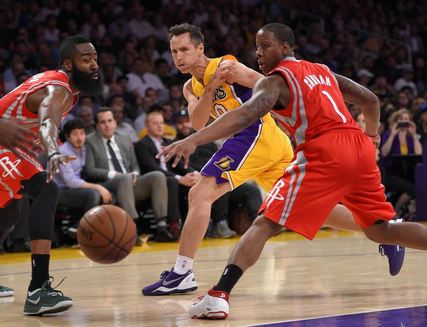Los Angeles Lakers guard Steve Nash, center, passes the ball as Houston Rockets guards James Harden, left, and Isaiah Canaan defend during the first half of an NBA basketball game, Tuesday, April 8, 2014, in Los Angeles. (AP Photo/Mark J. Terrill)