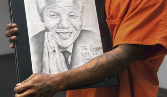ADVANCE FOR USE SUNDAY, APRIL 13 AND THEREAFTER - In this March 21, 2014 photo, a Champaign County Satellite Jail inmate and artist hold his favorite work, a portrait of Nelson Mandela, in his arms at the jail in Urbana, Ill. Jacqueline Archey, a Parkland College adult education instructor who recently taught GED classes at the jail, finds the artwork done by the inmates inspiring.  (AP Photo/The News-Gazette, John Dixon) MANDATORY CREDIT