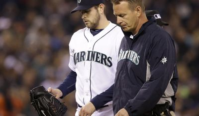 Seattle Mariners starting pitcher James Paxton, left, is accompanied by a trainer as he leaves the baseball game against the Los Angeles Angels in the sixth inning Tuesday, April 8, 2014, in Seattle. Paxton strained a muscled in his left side, the team said. (AP Photo/Elaine Thompson)