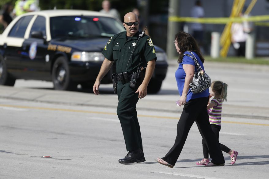 An Orange County Sheriff's deputy, left, escorts a mother and her child across a street after a vehicle crashed into a day care center, Wednesday, April 9, 2014, in Winter Park, Fla. At least 15 people were injured, including children. (AP Photo/John Raoux)