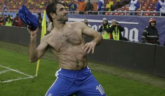 FILE - In this Nov. 19, 2013, file photo, Greece's Giorgos Karagounis celebrates after defeating Romania in their World Cup qualifying playoff second leg match at the National Arena in Bucharest. Greece captain Giorgos Karagounis remains motivator-in-chief at 37, playing in eight qualifiers and two playoffs to to reach a record 132 appearances. (AP Photo/Thanassis Stavrakis, File)