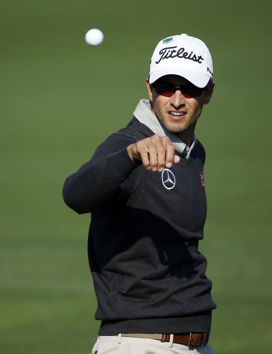 Adam Scott, of Australia, catches a ball from his caddie on the driving range during a practice round for the Masters golf tournament Wednesday, April 9, 2014, in Augusta, Ga. (AP Photo/Matt Slocum)