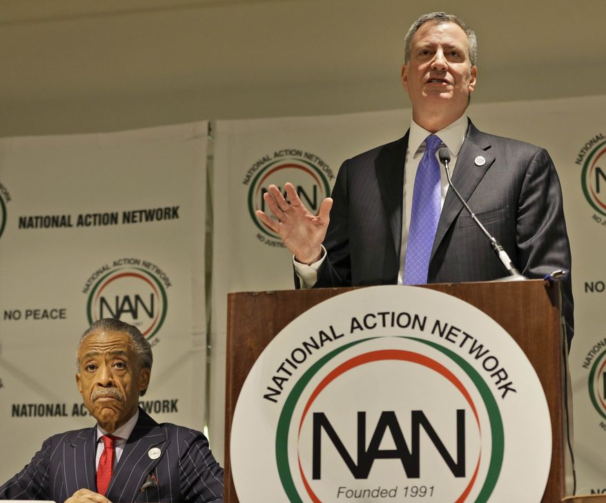 While Rev. Al Sharpton, left, listens, New York City Mayor Bill de Blasio speaks during the opening ceremonies of the National Action Network convention in New York, Wednesday, April 9, 2014. The 16th annual convention will run through April 12, 2014. (AP Photo/Seth Wenig)