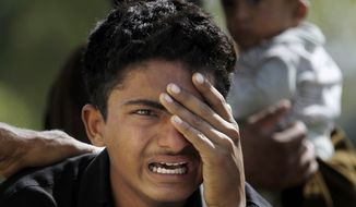 A Pakistani boy mourns over the death of his family member, a victim of bomb blast, outside a morgue in a local hospital in Islamabad, Pakistan, Wednesday, April 9, 2014. A bomb ripped through a fruit and vegetable market on the outskirts of the Pakistani capital of Islamabad on Wednesday morning, killing scores of people and leaving dozens more wounded, officials said. (AP Photo/Anjum Naveed)