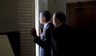 President Barack Obama peers out a window with then-Press Secretary Robert Gibbs in the Doheny Memorial Library to scope out the crowd size at a rally at the University of Southern California Alumni Park in Los Angeles, Calif., Oct. 22, 2010. (Official White House Photo by Pete Souza)