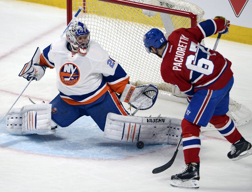 New York Islanders goalie Evgeni Nabokov (20) stops Montreal Canadiens left wing Max Pacioretty during the second period of an NHL hockey game Thursday, April 10, 2014, in Montreal. (AP Photo/The Canadian Press, Ryan Remiorz)
