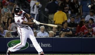 Atlanta Braves' Justin Upton hits a two-run home run to score teammate Freddie Freeman in the third inning of a baseball game against the New York Mets, Thursday, April 10, 2014, in Atlanta. (AP Photo/David Goldman)