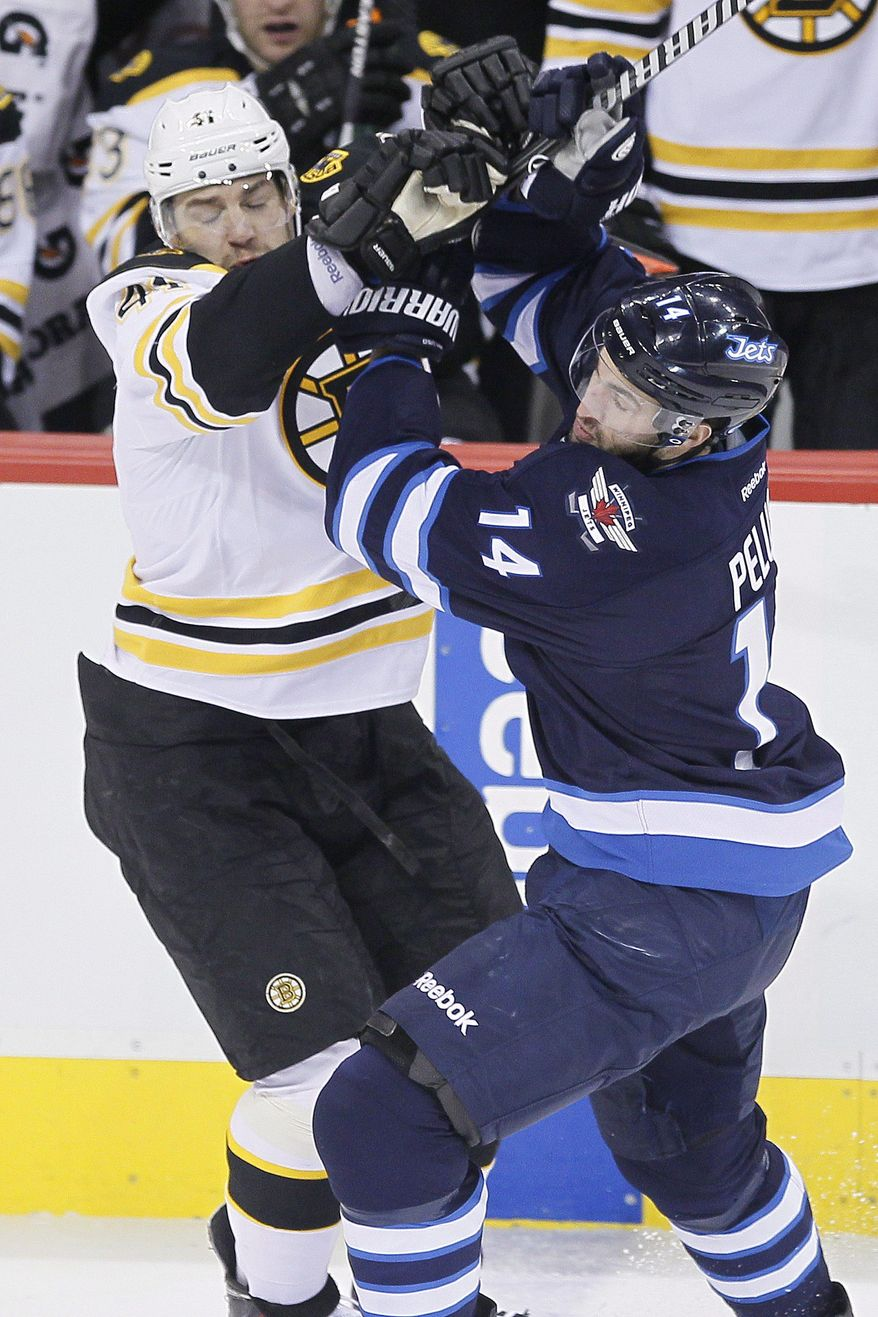 Boston Bruins' Andrej Meszaros (41) mixes it up with Winnipeg Jets' Anthony Peluso (14) during the first period of an NHL hockey game Thursday, April 10, 2014, in Winnipeg, Manitoba. (AP Photo/The Canadian Press, John Woods)