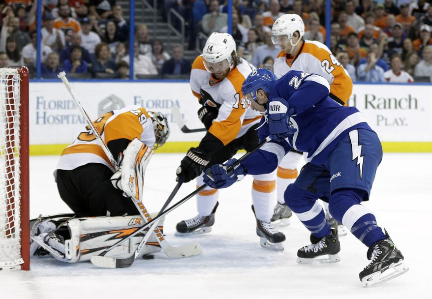 Tampa Bay Lightning right wing Ryan Callahan (24) attempts to stuff the puck past Philadelphia Flyers goalie Ray Emery (29) as center Sean Couturier (14) and right wing Matt Read (24) defend during the second period of an NHL hockey game Thursday, April 10, 2014, in Tampa, Fla. (AP Photo/Chris O'Meara)