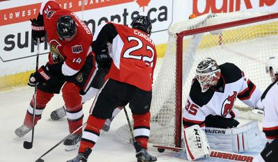 Ottawa Senators' Colin Greening (14) and Erik Condra (22) and New Jersey Devils goaltender Cory Schneider (35) look for the puck at the side of the net during first-period NHL hockey game action in Ottawa, Ontario, Thursday, April 10, 2014. (AP Photo/The Canadian Press, Fred Chartrand)