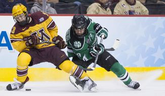 Minnesota's Taylor Cammarata, left, battles with North Dakota's Rocco Grimaldi, right, for the puck during the second period of an NCAA men's college hockey Frozen Four tournament game on Thursday, April 10, 2014, in Philadelphia. (AP Photo/Chris Szagola)