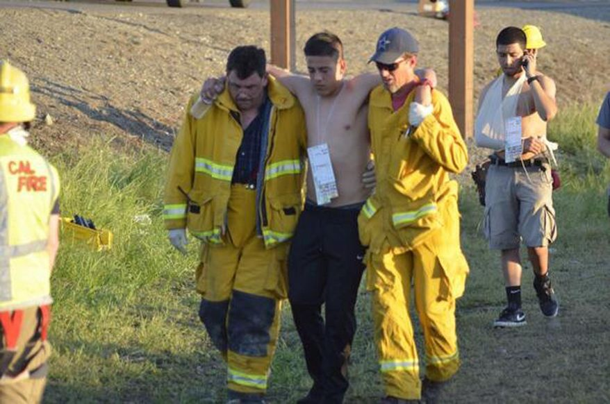 Rescuers tend to walking wounded after a fiery crash involving several vehicles, Thursday, April 10, 2014, just north of Orland, Calif., that left at least nine dead. Authorities said it is not yet clear what caused the crash but that it involved a tour bus, a FedEx truck and a Nissan Altima. (AP Photo/The Chico Enterprise-Record, Dan Reidel)