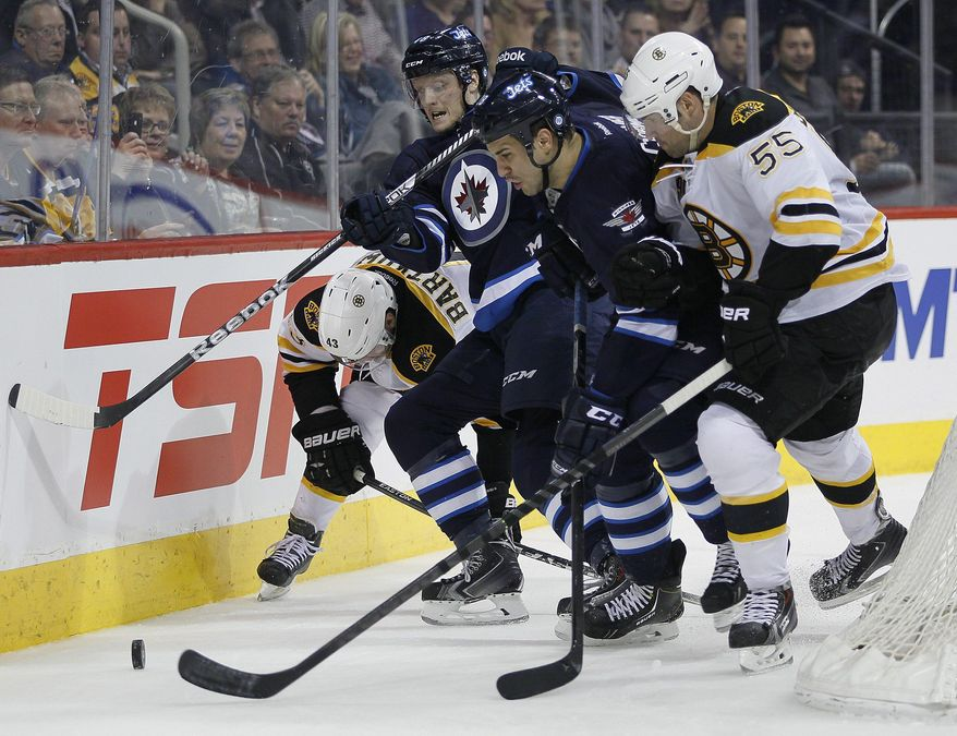 Boston Bruins' Matt Bartkowski (43) and Johnny Boychuk (55) scramble with Winnipeg Jets' Carl Klingberg, center left, and Patrice Cormier for the puck behind the Bruins' net during the second period of an NHL hockey game Thursday, April 10, 2014, in Winnipeg, Manitoba. (AP Photo/The Canadian Press, John Woods)