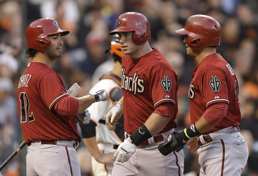 Arizona Diamondbacks' Paul Goldschmidt, center, is congratulated by Eric Chavez, left, and Martin Prado after Goldschmidt hit a three run home run off San Francisco Giants' Tim Lincecum in the first inning of a baseball game Wednesday, April 9, 2014, in San Francisco. (AP Photo/Ben Margot)