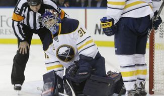 Official Brad Meier checks on Buffalo Sabres goalie Matt Hackett after Hackett was hit by the puck during the second period of an NHL hockey game against the New York Rangers on Thursday, April 10, 2014, in New York. (AP Photo/Frank Franklin II)