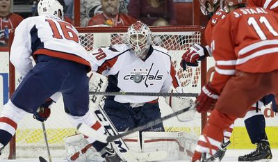 Washington Capitals goalie Braden Holtby (70) and Eric Fehr (16) defend the goal against Carolina Hurricanes' Eric Staal (12) and Jordan Staal (11) during the first period of an NHL hockey game in Raleigh, N.C., Thursday, April 10, 2014. (AP Photo/Gerry Broome)