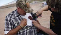 """Krissy Thornton, right, looks at blood from a taser wound on Ammon Bundy near Bunkerville, Nev. Wednesday, April 9, 2014. Bundy was tasered by Bureau of Land Management law enforcement officers while protesting the roundup of what the BLM calls """"trespass cattle"""" that rancher Cliven Bundy grazes in the Gold Butte area 80 miles northeast of Las Vegas. (AP Photo/Las Vegas Review-Journal, John Locher)"""