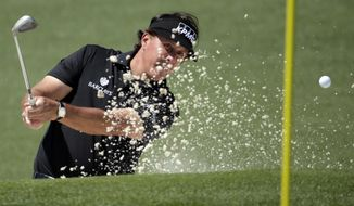 Phil Mickelson hits out of a bunker on the second hole during the first round of the Masters golf tournament Thursday, April 10, 2014, in Augusta, Ga. (AP Photo/Chris Carlson)