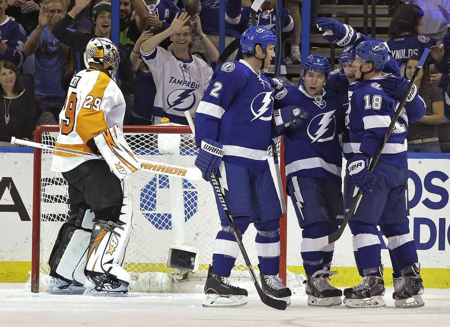 Tampa Bay Lightning center Tyler Johnson (9) celebrates with teammates Eric Brewer (2) and Ondrej Palat (18), of the Czech Republic, after scoring past Philadelphia Flyers goalie Ray Emery (29) during the first period of an NHL hockey game Thursday, April 10, 2014, in Tampa, Fla. (AP Photo/Chris O'Meara)