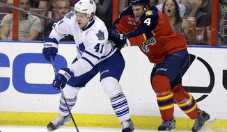 Toronto Maple Leafs left wing Nikolai Kulemin (41) prepares to shoot as Florida Panthers defenseman Dylan Olsen (4) moves in during the first period of an NHL hockey game on Thursday, April 10, 2014, in Sunrise, Fla. (AP Photo/Lynne Sladky)